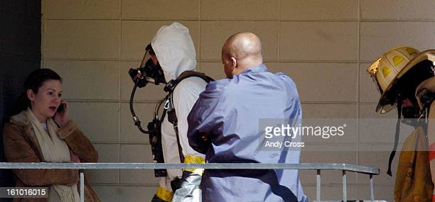 COMARCH 16TH 2005 Denver Firefighters Hazmat crew walk past a resident of the Montmartre high rise building Wednesday afternoon while investigating...