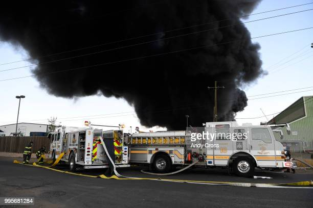 Denver firefighters rush to hook up hoses to try to get control of a fire in a large pile of crushed vehicles near 5600 York St July 10 2018