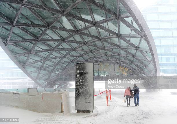 A Denver International Airport employee right escorts a woman over to the Westin Hotel in bitter winds and heavy snow at Denver International Airport...