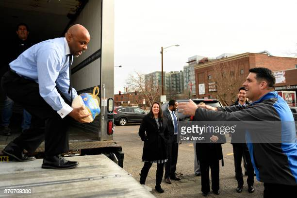 Denver Mayor Michael B Hancock makes a low catch on a toss from Matt Ciruilli the program manager for AECOM as he helps the Denver Rescue Mission...