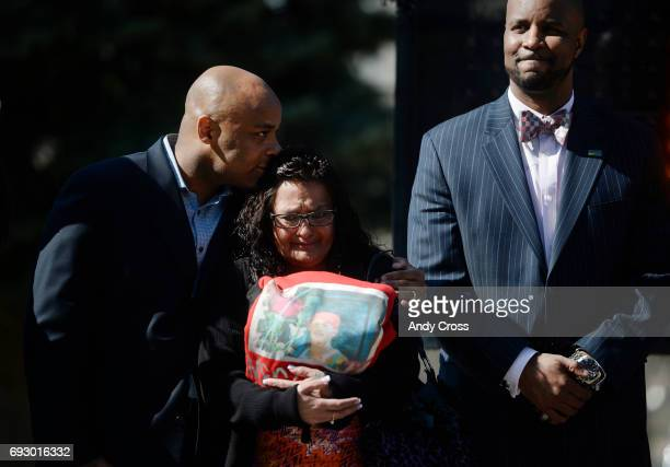 Denver Mayor Michael Hancock left comforts Linda Limon Medina center who holds a tshirt with her son Jose on it during HB141191 Bill signing on the...