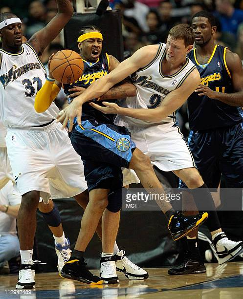 Denver Nuggets Allen Iverson looses the ball while be defended by Washington Wizards Andray Blatche and Darius Songaila during their game played at...