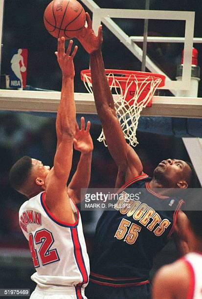 Denver Nuggets' center Dikembe Mutombo blocks a layup by New Jersey Nets' PJ Brown in first half action 21 March The Nets led 6353 in the third...