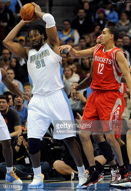 Denver Nuggets center Nene grabs a rebound away from Houston Rockets shooting guard Kevin Martin during the first quarter on Monday January 3 2011 at...