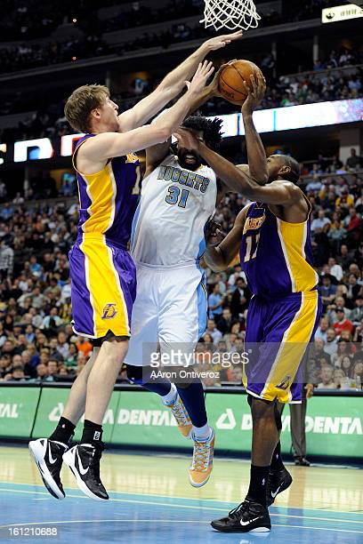 Denver Nuggets center Nene Hilario is fouled by Los Angeles Lakers power forward Troy Murphy as center Andrew Bynum provides help defense during the...