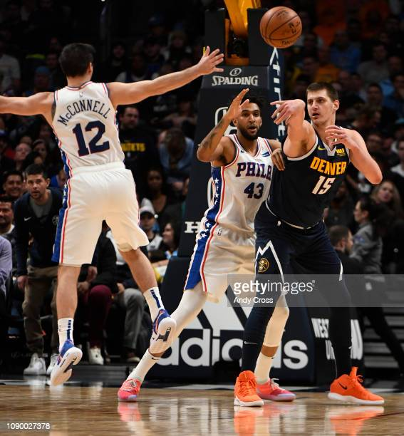 Denver Nuggets center Nikola Jokic passes the ball to the back court against Philadelphia 76ers forward Jonah Bolden and Philadelphia 76ers guard TJ...