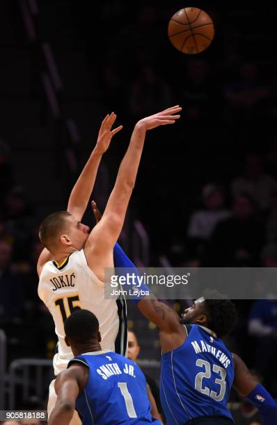 Denver Nuggets center Nikola Jokic takes a shot as Dallas Mavericks guard Wesley Matthews sticks his hand in his face during the fourth quarter on...