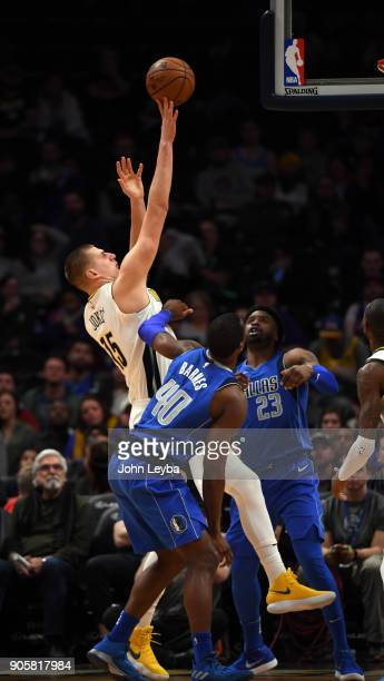 Denver Nuggets center Nikola Jokic takes a shot over Dallas Mavericks forward Harrison Barnes and guard Wesley Matthews during the fourth quarter on...