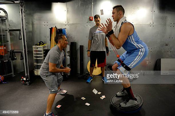 Denver Nuggets Danilo Gallinari balances on a balancing ball catching playing cards that are tossed by assistant coach/strength and conditioning...