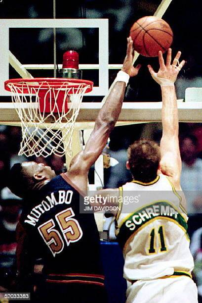 Denver Nuggets Dikembe Mutombo blocks the shot attempt by SuperSonic Detlaf Schrempf during overtime action 07 May 1994 in Seattle. Denver won 98-94.