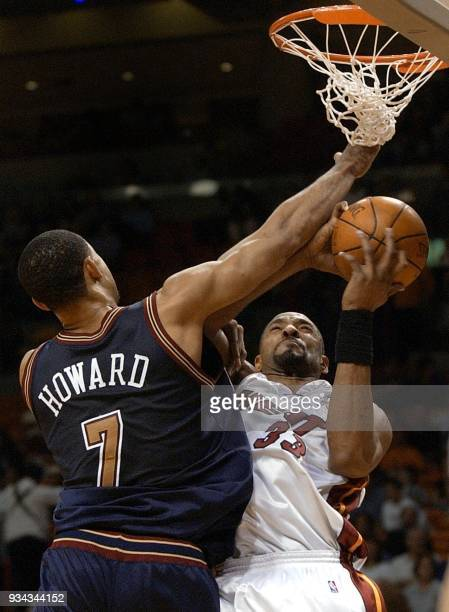 Denver Nuggets forward Juwan Howard fouls Miami Heat center Alonzo Mourning in the first half 16 March 2002 at the American Airlines Arena in Miami...