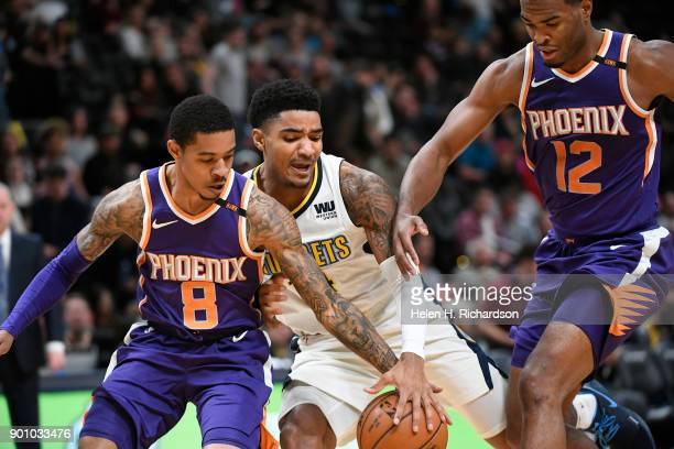 Denver Nuggets guard Gary Harris #14 fights for the ball against Phoenix Suns' guards Tyler Ulis #8 left and TJ Warren #12 right during the first...