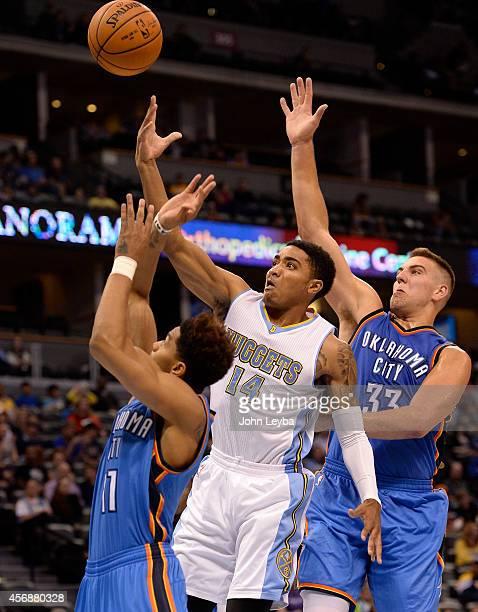 Denver Nuggets guard Gary Harris drives to the basket between Oklahoma City Thunder guard Jeremy Lamb and Oklahoma City Thunder forward Mitch McGary...