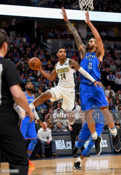 Denver Nuggets guard Gary Harris flies through the air past Oklahoma City Thunder center Steven Adams to throw a pass to the outside during the first...