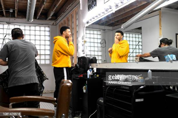 Denver Nuggets guard Jamal Murray checks his fresh work in the mirror after being worked on by barber Josue 'Sway' Navarro works on at Bellwether...