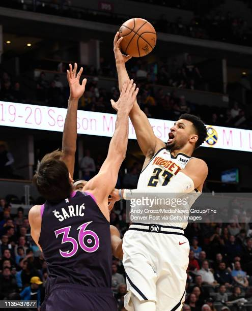 Denver Nuggets guard Jamal Murray lays up a shot but is fouled by Minnesota Timberwolves forward Dario Saric in the first half at Pepsi Center March...