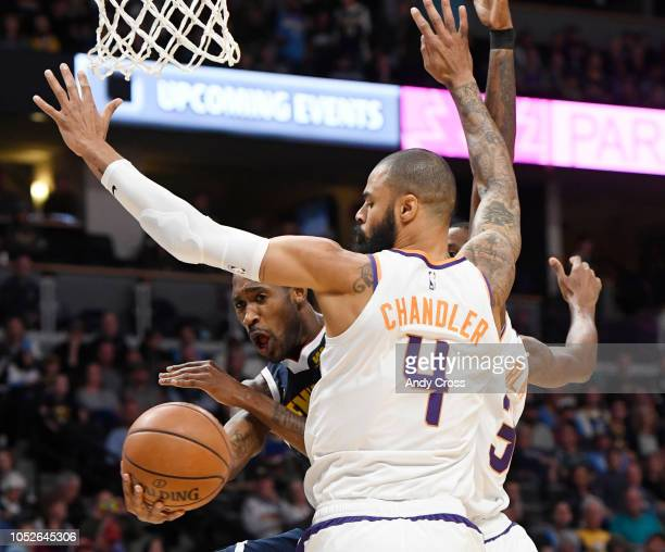 Denver Nuggets guard Will Barton gets a pass around Phoenix Suns center Tyson Chandler and Phoenix Suns forward Trevor Ariza in the first quarter at...