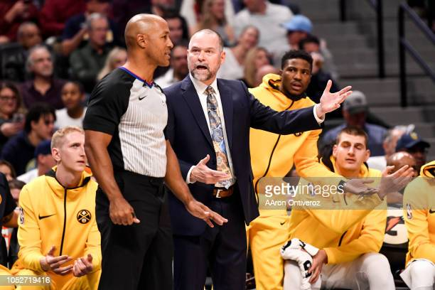 Denver Nuggets head coach Michael Malone speaks to a referee about whether a foul on the Golden State Warriors was a shooting foul during the first...