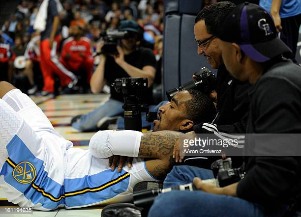 Denver Nuggets shooting guard JR Smith lays on a photographer after being fouled by Atlanta Hawks small forward Damien Wilkins during the second half...