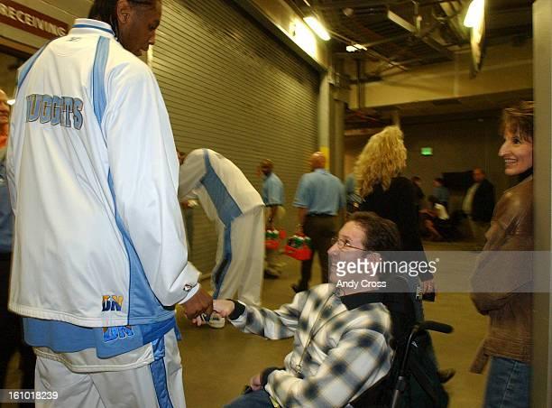 DENVER CO APRIL 24 2004 Denver Nuggets vs Minnesota Timberwolves playoffs Carmelo Anthony left greets Nicholas<cq> Owens<cq> right and his mother...