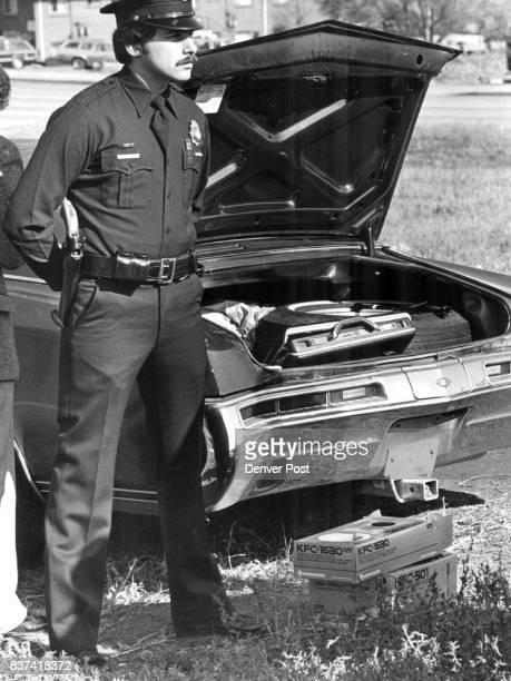 Denver Patrolman MS Drajem stands guard over a car with a suspected stolen briefcase in the trunk Credit The Denver Post