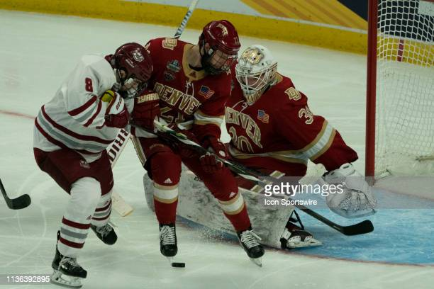 Denver Pioneers Defenseman Michael Davies and Massachusetts Minutemen Forward Bobby Trivigno battle to control the puck in front of Denver Pioneers...
