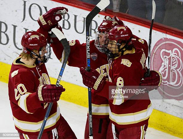 Denver Pioneers forward Danton Heinen and Denver Pioneers forward Trevor Moore celebrate with defenseman Adam Plant center after Plant's goal against...