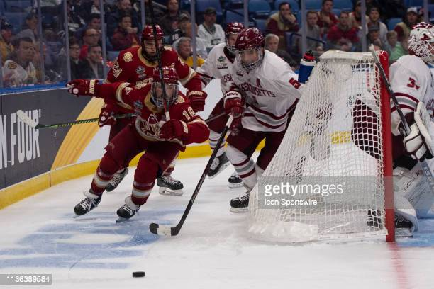 Denver Pioneers Forward Jake Durflinger and Massachusetts Minutemen Defenseman Mario Ferraro chase after the puck during the overtime period of the...