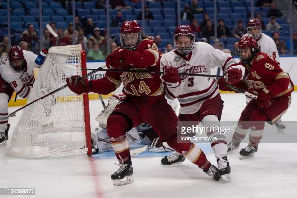 Denver Pioneers Forward Jarid Lukosevicius and Massachusetts Minutemen Defenseman Ty Farmer chase after the puck during the overtime period of the...