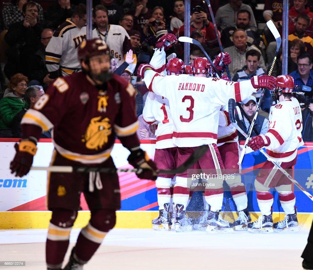 Denver Pioneers forward Jarid Lukosevicius (14) celebrates his third goal with Denver Pioneers forward Dylan Gambrell (7) Denver Pioneers defenseman Tariq Hammond (3) and Denver Pioneers defenseman Michael Davies (21) during the second period against the Minnesota-Duluth Bulldogs of the NCAA Men's Ice Hockey Championship on April 8, 2017 in Chicago, Illinois at the United Center.