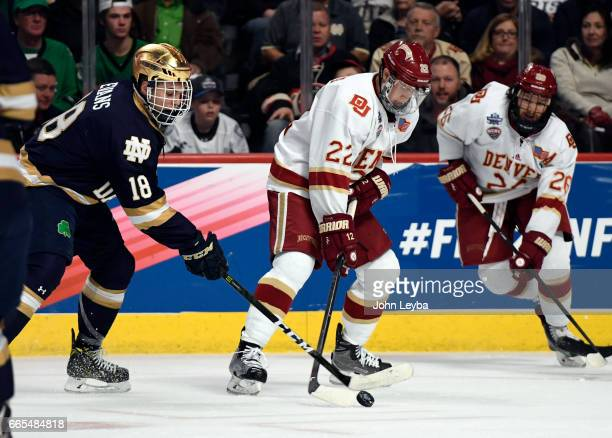 Denver Pioneers forward Logan O'Connor controls the puck from Notre Dame Fighting Irish forward Jake Evans during the first period on April 6, 2017...