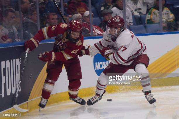 Denver Pioneers Forward Tyler Ward and Massachusetts Minutemen Defenseman Jake McLaughlin battle for the puck during the second period of the NCAA...