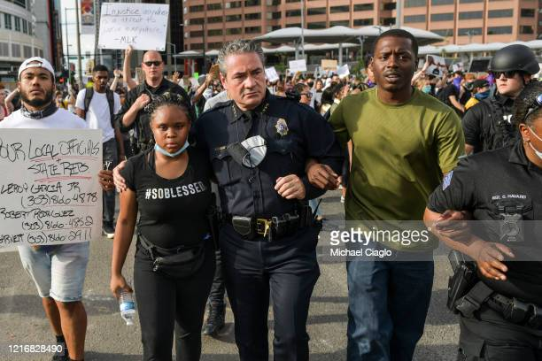 Denver Police Chief Paul Pazen embraces a woman as he marches with thousands of protesters during the fifth consecutive day of demonstrations in the...