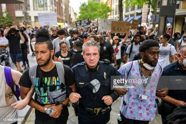 Denver Police Chief Paul Pazen links arms with people protesting the death of George Floyd on June 1 2020 in Denver Colorado Protests continue in...