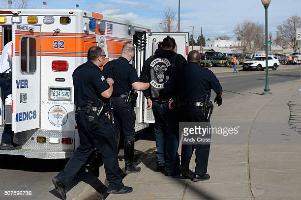 Denver Police escort a man in handcuffs away from the National Western Stock Show complex and into an ambulance January 30 2016 DPD reported a...