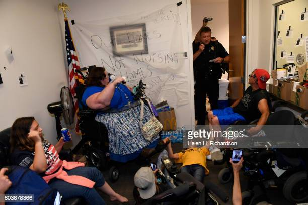 Denver police officer asks protesters including Carrie Ann Lucas seated in a wheelchair to vacate the offices of Senator Cory Gardner or risk getting...