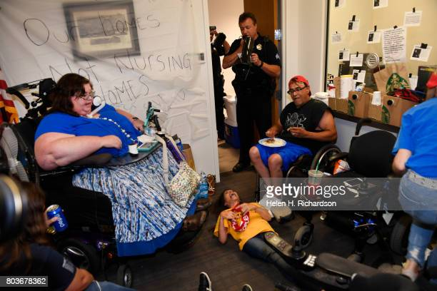 Denver police officer asks protesters including Carrie Ann Lucas left to vacate the offices of Senator Cory Gardner or risk getting arrested on June...