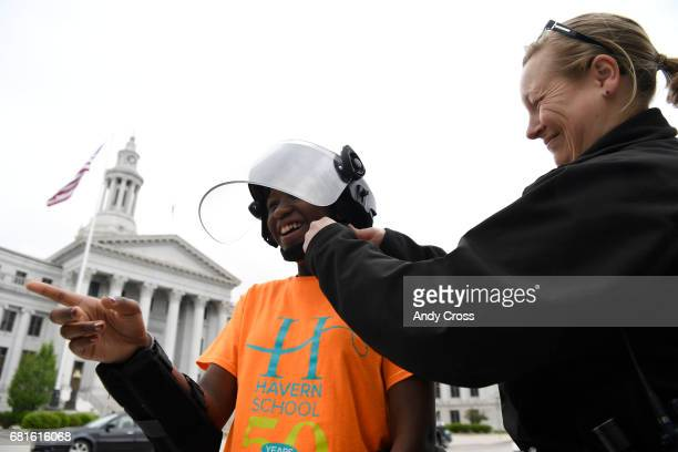 Denver Police officer Jennifer Couch with Denver Police Community Relations buckles up a police riot helmet for Havern School student Jess Loch in...
