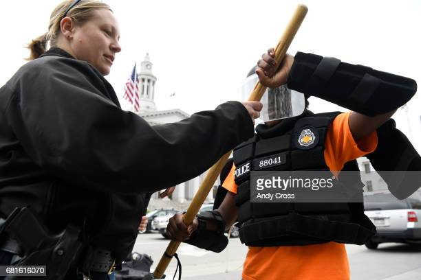 Denver Police officer Jennifer Couch with Denver Police Community Relations shows Havern School student Jess Loch what it's like to wear and use riot...