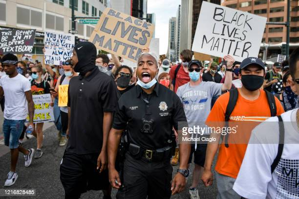 Denver Police officer Nate Magee chants with protesters marching during the fifth consecutive day of demonstrations in the aftermath of the death of...