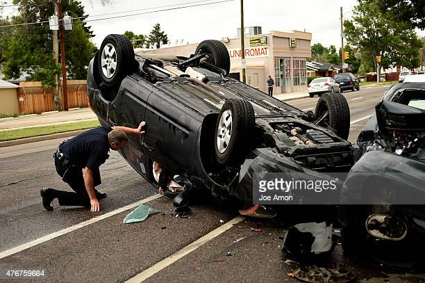 A Denver Police officer talks to the single occupant in a vehicle that clipped a parked car and flipped on 31st Ave near Williams in Denver June 11...