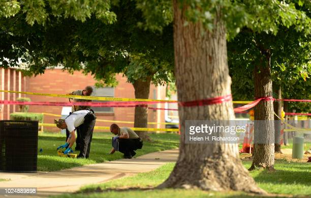 Denver police officers look over the scene of a shooting that happened at 3200 North Marion Street on August 28 in Denver Colorado A teenage boy was...