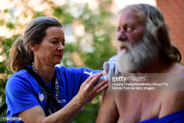 Denver Public Health nurse Maggie McClean left gives a shot of hepatitis A vaccines to David May by Stout Street Health Center in Denver on July 24...