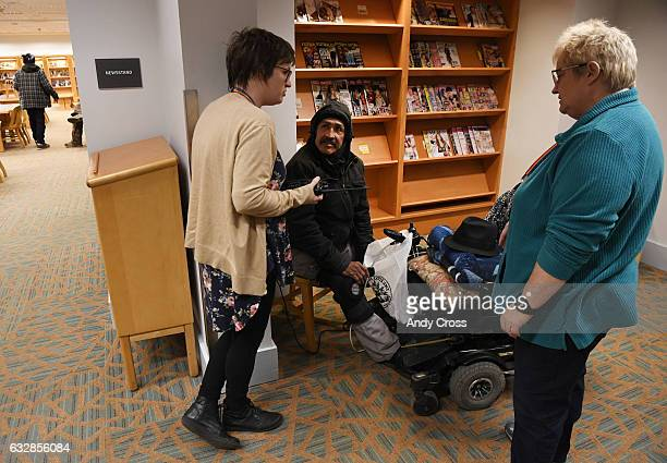 Denver Public Library community resource specialist Kristi Schaefer left and resource navigator Sarah Humble talk and try to help out Richard Ortega...
