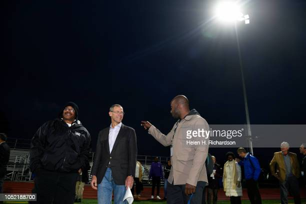 Denver Public Schools superintendent Tom Boasberg middle checks out the new lights on the football field with football coach Tony Lindsay left and...