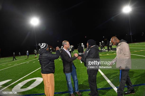 Denver Public Schools superintendent Tom Boasberg second from left shakes hands with football coach Tony Lindsay second from right as they check out...