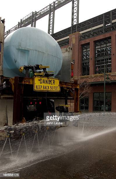 Denver Public Works truck sprays magnesium chloride down on Blake street in front of Coors Field as the city prepares for the snow fall