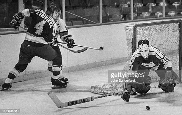 DEC 24 1975 DEC 29 1975 Denver Spurs Garry Lariviere and Ralph Backstrom watch as goalie Jack ***** dives at puck Phoenix Defense has Everything...