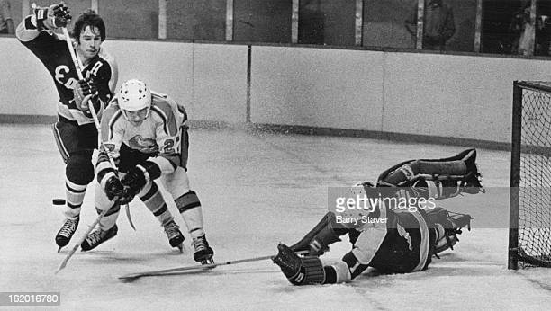 MAR 23 1975 Denver Spurs It Was this Kind of Night for Denver's Spurs at Coliseum Spurs' Brian Ogilvie has puck batted harmlessly out of way by...
