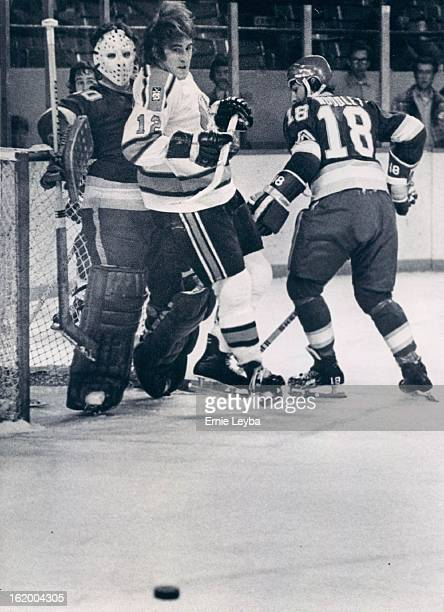 Denver Spurs ; Spur Wing Meets Unfriendly Reception Committee; Butch Williams of the Denver Spurs gets the old sandwich treatment from Phoenix goalie...